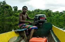 Boy from the Ndyuka tribe navigating a boat in the jungle of Suriname