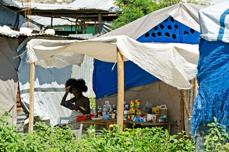 Woman combing her hair in a Haitian refugee camp